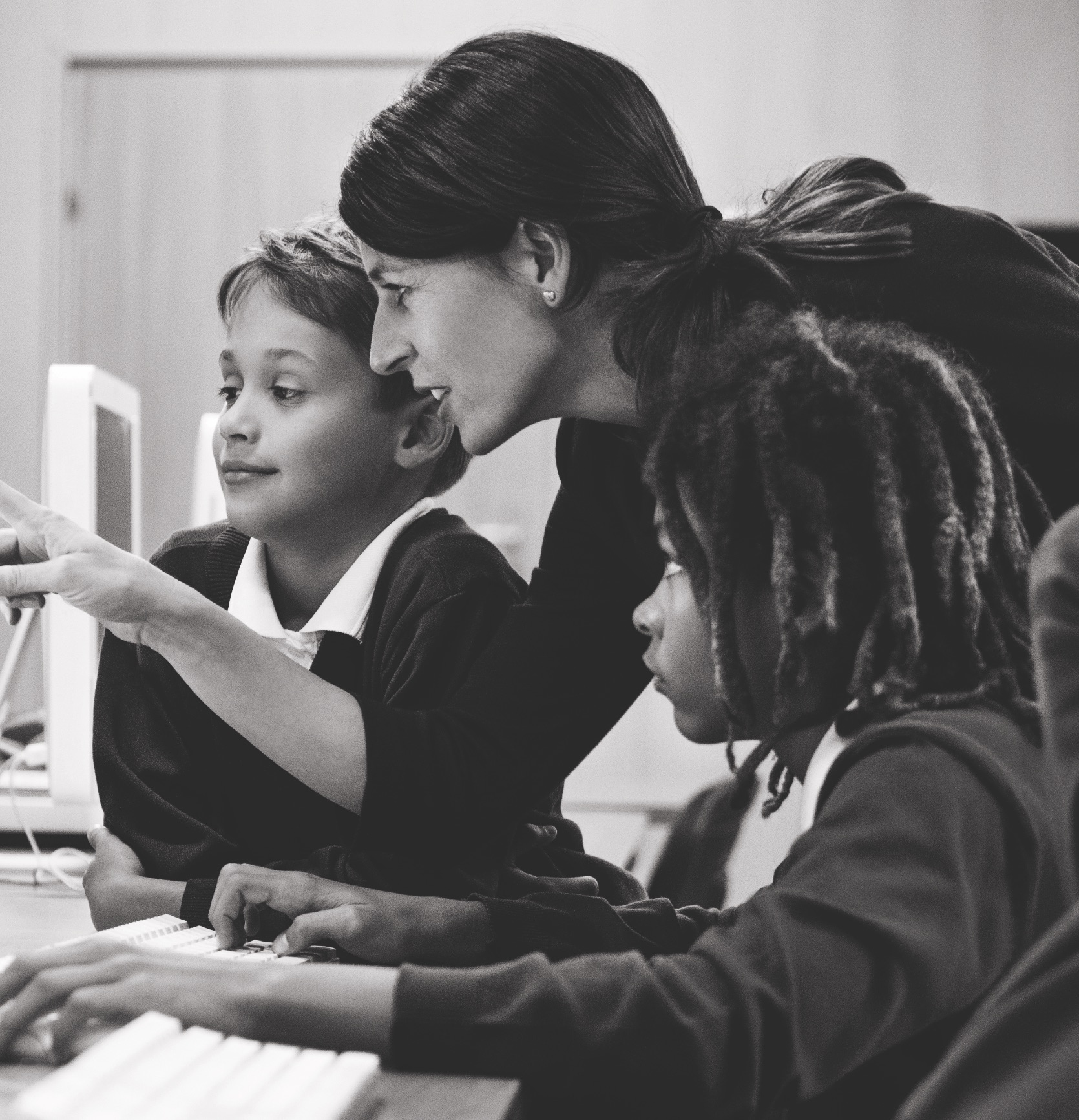 Teacher assisting two students at a computer